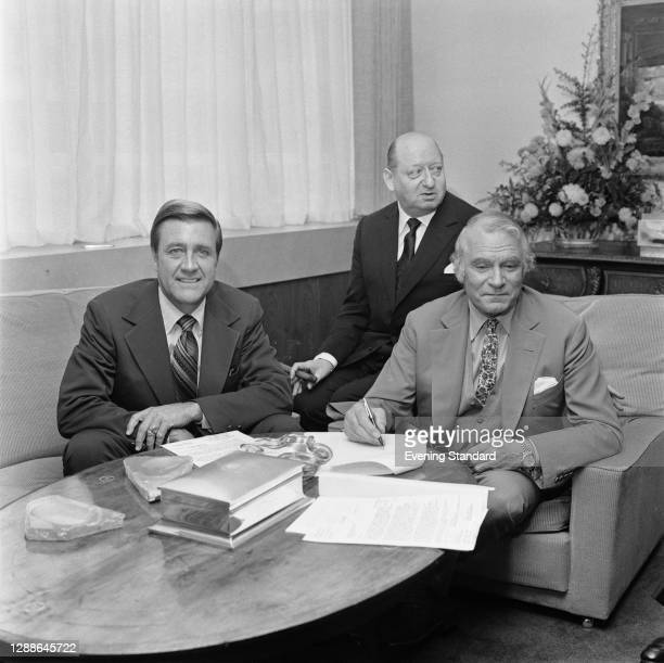 From left to right, American entertainment executive Martin Starger signs a deal with British TV head Lew Grade and actor Sir Laurence Olivier, UK,...