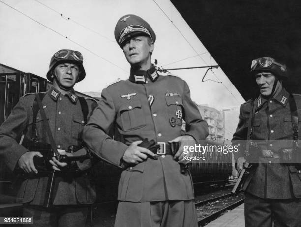 From left to right American singer and actor Frank Sinatra Irish actor Edward Mulhare and English actor Trevor Howard dressed as German soldiers for...