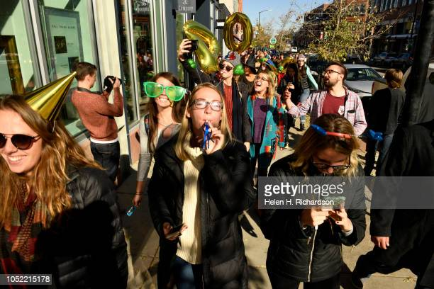 From left to right Anna Wood Lana Morgan and Erika Gulija all with New Era Colorado blow horns and cheer as they parade down Pearl Street dressed in...