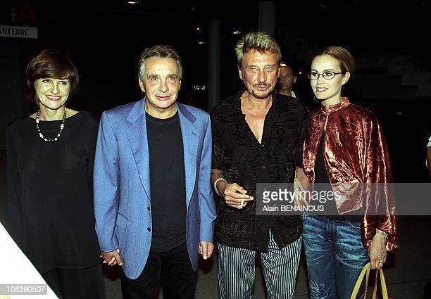 From left to right AnneMarie Perier Michel Sardou Johnny Hallyday Laeticia in Paris France on September 16 2000