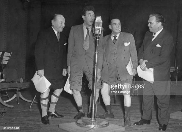 From left to right band leader Billy Ternent comedian Frankie Howerd variety star Jimmy James and holiday camp mogul Billy Butlin hold a knobbly knee...