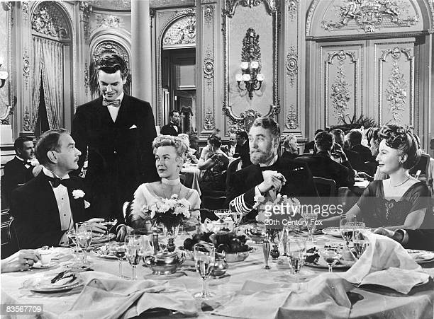 From left to right Clifton Webb Robert Wagner Frances Bergen Brian Aherne and Barbara Stanwyck talk over dinner in a scene from the film 'Titanic'...