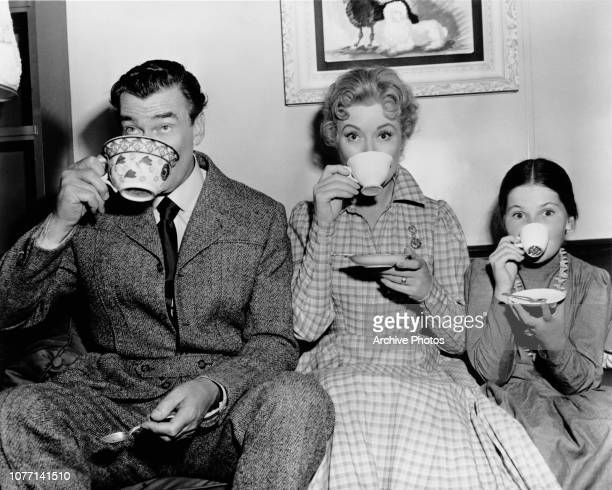 From left to right costars Walter Pidgeon Greer Garson and Donna Corcoran drinking tea on the set of the MGM film 'Vicki' aka 'My Mother and Mr...