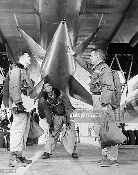 From left to right Defence Systems Operator W G Griswold Flight Engineer G C Tate and Pilot 'Doc' Witchell inspect the detachable pod of the US Air...