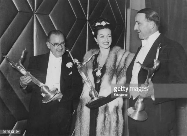 From left to right director Herbert Wilcox actress Margaret Lockwood and studio head J Arthur Rank with their awards during the National Film Awards...