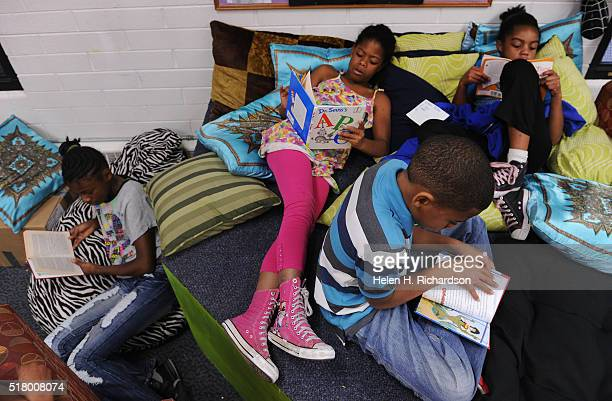 From left to right Doresca Wilkerson Nautica Hughes in pink her brother Stanley 9 and Le'Asia Polidore right read during the afternoon at the Denver...