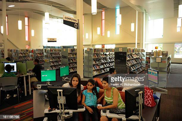 From left to right Estefany Plazola 15 and her sister Jennifer 10 help their mother Alma right on the computer The new Green Valley Ranch library was...
