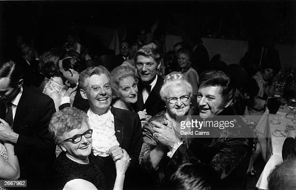 From left to right female impersonator and restauranter Danny La Rue TV presenter and actor Peter Murray and pianist Liberace dancing with their...