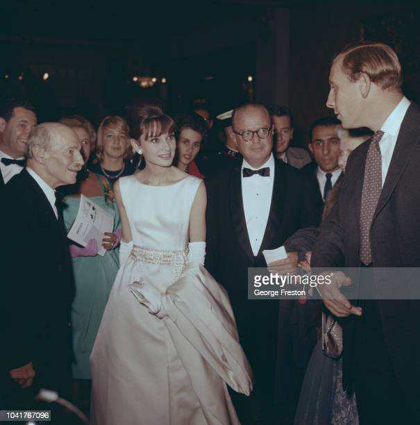 From left to right former British Prime Minister Lord Attlee actress Audrey Hepburn and George Weltner of Paramount Pictures at a charity premiere of...