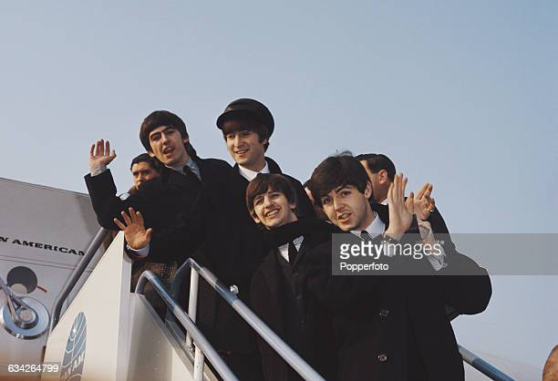 George Harrison John Lennon Ringo Starr and Paul McCartney of English pop group The Beatles pictured together on the steps of a Pan American 707 jet...