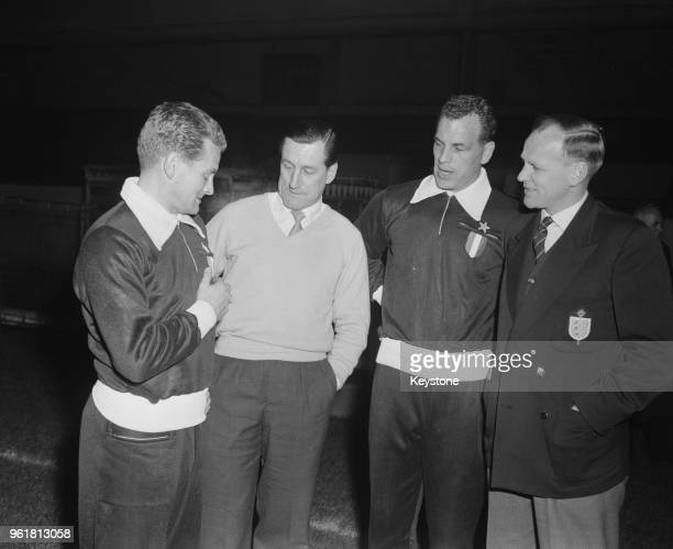 From left to right, Giampiero Boniperti, captain of the Italian football team Juventus F. C. Shows his club badge to Arsenal manager George Swindin ,...