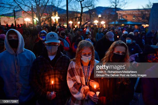 From left to right: Iain Griffith, Elliot Mahoney, Gabi Brown and Maya Colombo-Hamilton, all 18, take part in a candlelight vigil to honor the ten...