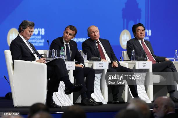 From left to right John Micklethwait editorinchief at Bloomberg News Emmanuel Macron France's president Vladimir Putin Russia's president and Shinzo...