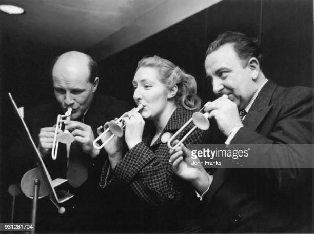 From left to right, Joseph Beachus, composer Madeleine Dring and opera singer Owen Brannigan rehearse on their tiny instruments for an April Fool's...