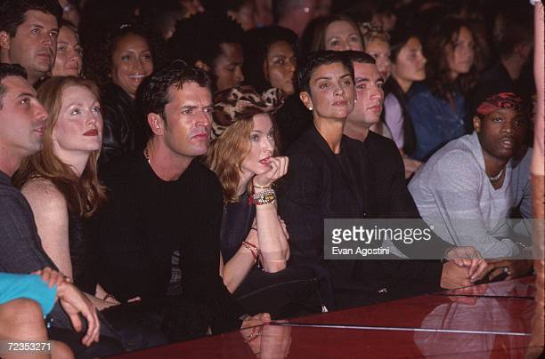 From left to right Julianne Moore Rupert Everett Madonna and Ingrid Casares attend the Versace Versus fashion show September 12 1999 in New York City
