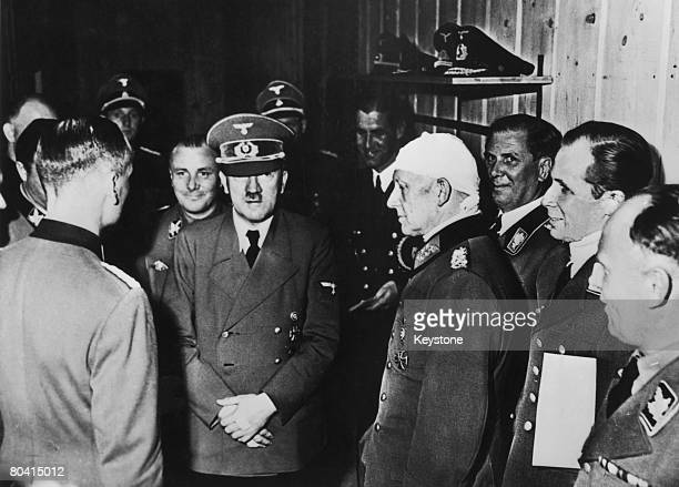 From left to right Martin Bormann Adolf Hitler Alfred Jodl A Borman Below and Captain Baur at Hitler's headquarters in Rastenburg East Prussia after...
