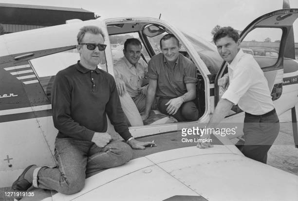 From left to right, motorcycle racers Jack Ahearn , Frank Perris , Mike Hailwood and Jim Redman with an aircraft at Biggin Hill Aerodrome after the...