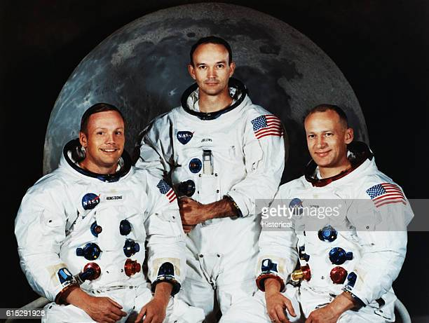 From left to right Neil Armstrong Michael Collins and Buzz Aldrin Jr pose for a portrait in their space suits in front of a backdrop showing the Moon...