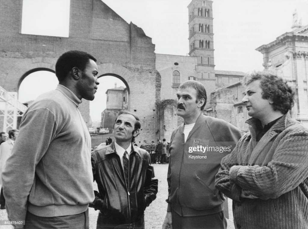 From left to right, Olympic champion Rafer Johnson, singer Charles Aznavour and actor Stanley Baker (1928 - 1976), with director Michael Winner near the Colosseum in Rome, Italy, for the location filming of 'The Games', circa 1970.