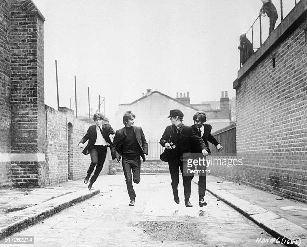 From left to right, Paul McCartney, George Harrison, John Lennon, and Ringo Starr run down an empty London street in a scene from the movie A Hard...