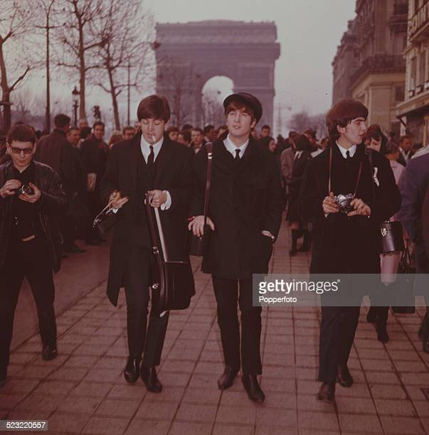 Paul McCartney John Lennon and George Harrison from The Beatles walk down the Avenue des ChampsElysees in Paris France in January 1964