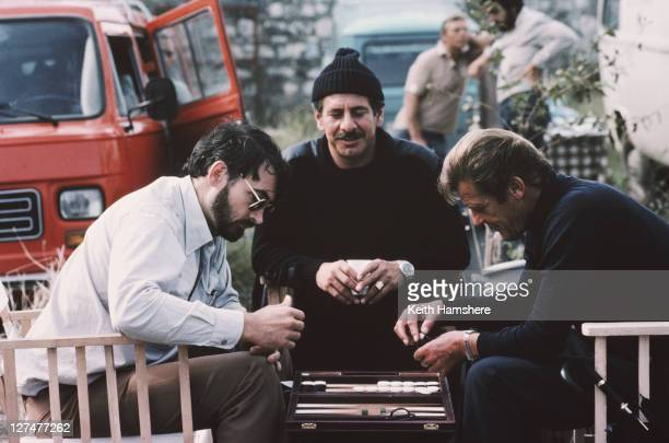 From left to right producer and screenwriter Michael G Wilson plays backgammon with Israeli actor Topol and English actor Roger Moore on the set of...