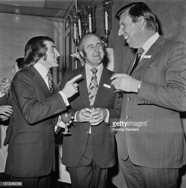 From left to right, racing drivers Jackie Stewart, Denny Hulme and Ken Tyrrell socialising at an event, UK, 23rd November 1973.