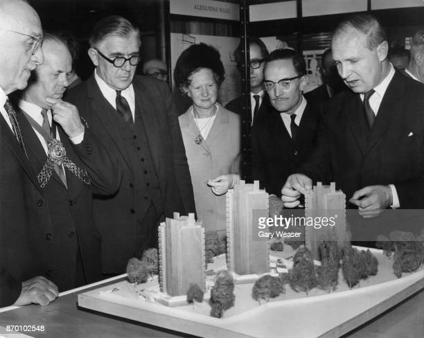 From left to right Richard Crossman Mrs Carr Councillor Fagin and Borough architect Edward Hollamby examine a model of the Pentagon block on Solon...
