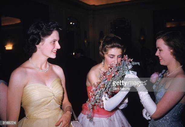 From left to right the Honourable Diana Herbert Miss Jane Sheffield and Frances Sweeney daughter of the Duchess of Argyll attend a debutante party...