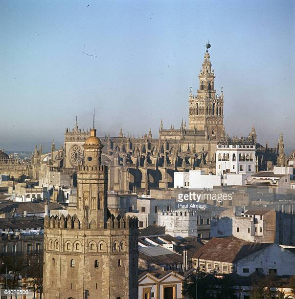 From left to right the Torre del Oro or Tower of Gold the cathedral and La Giralda tower in Seville Spain