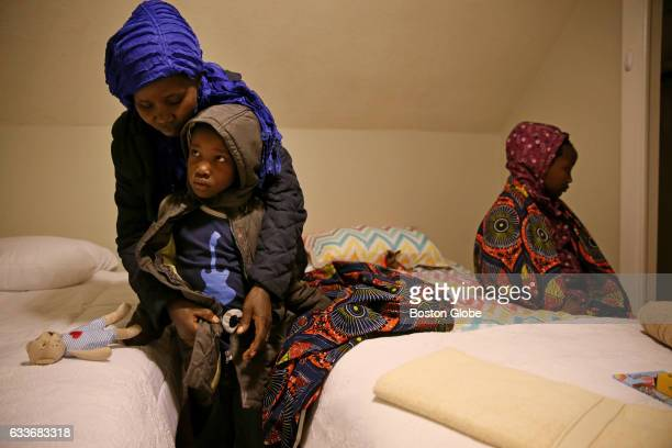 From left Vanisi Uzamukunda helps her daughters Sarah and Lea get ready for bed at their new home in Lowell Mass on Feb 03 2017 Members of the...