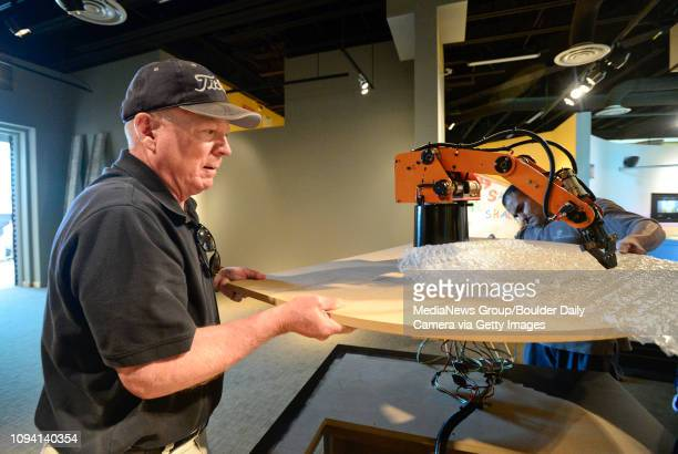 Volunteer Patrick McCoy and custodian Fermin Uriarte carefully move part of a robotics exhibit at the Longmont Museum and Cultural Center on Thursday...