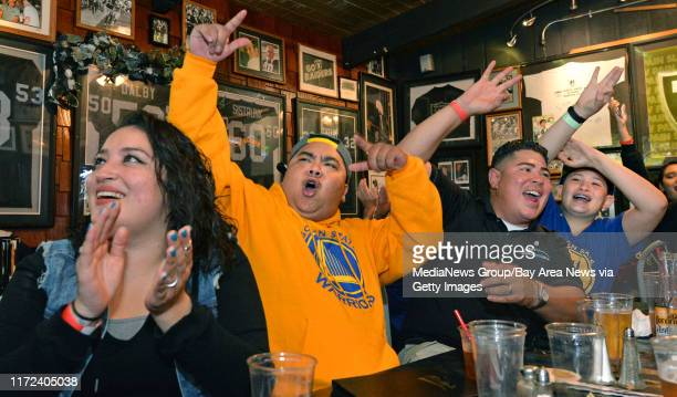 From left Warriors fans Ivana Ramos of San Leandro Jesse Mangabay of San Leandro Miguel Lopez of Hayward and his son Matthew Lopez of Hayward cheer...