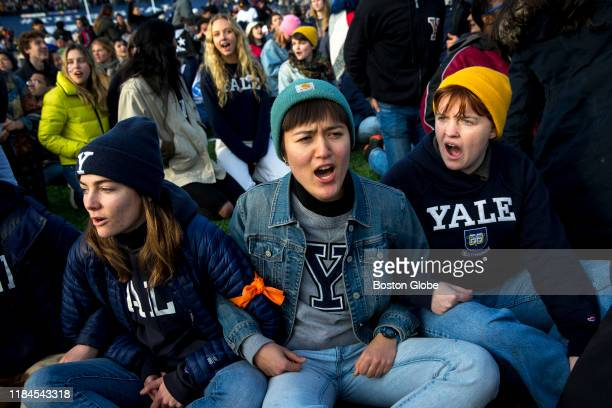 From left, Yale senior Nadia Grisaru, senior Sarah Adams and sophomore Lillian Burton protest during the halftime of the college football game...