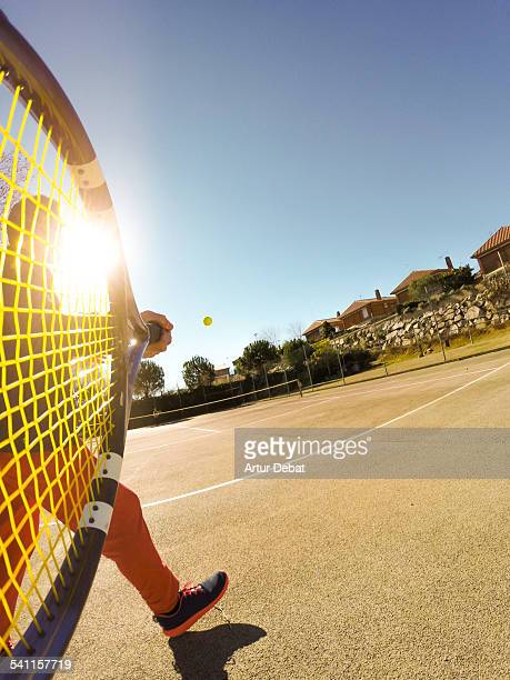 POV from racket of man playing tennis with sun.