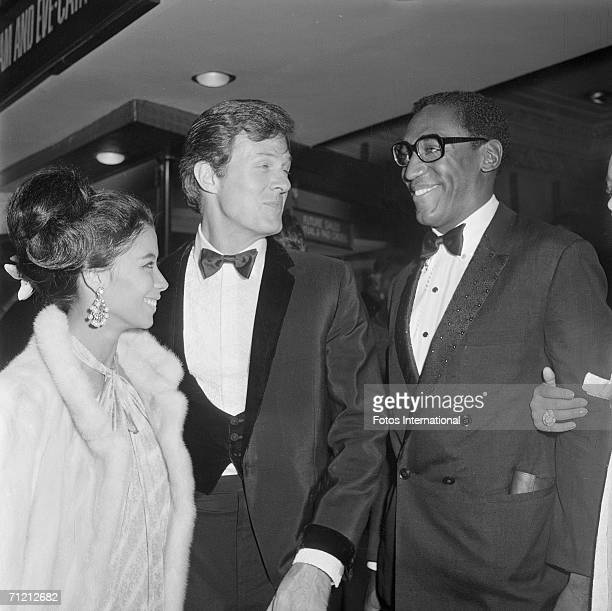 From right American comedian Bill Cosby actor Robert Culp and Camille Crosby Bill Cosby's wife stand together as they attend the premiere of the...