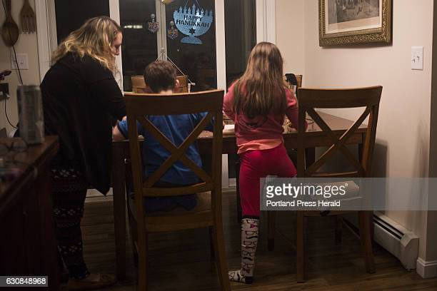From right Roxy Rovin Everett Rovin and their Mom Amy Starr bake and decorate Hanukkah cookies at their home in Gorham The family is also helping...
