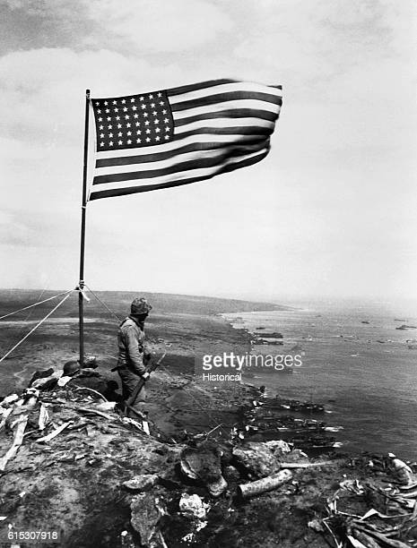 From the crest of Mount Suribachi the Stars and Stripes wave in triumph over Iwo Jima after US Marines had fought their way inch by inch up its steep...