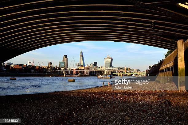 CONTENT] From the foreshore beach of the River Thames at low tide framed by Blackfriars Bridge the new skyline of the City of London is viewed on a...