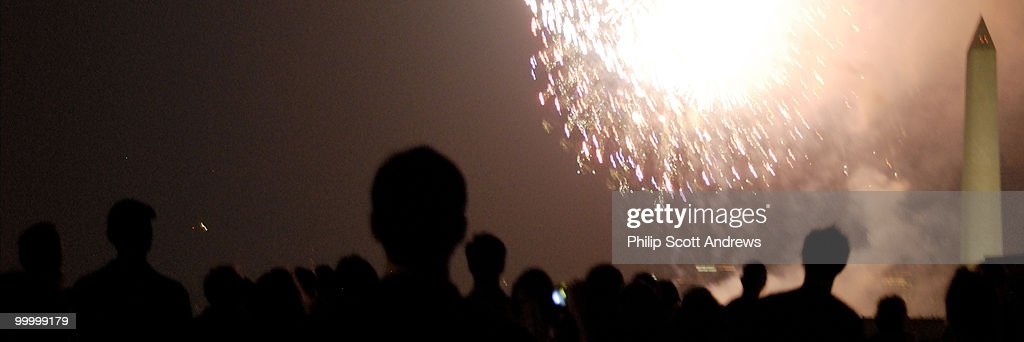 From the top of a 7th St. Sw office building, spectators watch the Fourth of July fireworks on the Mall.