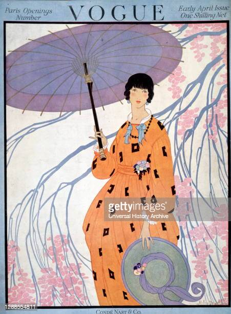 Front cover of vogue magazine, early April issue, published by Cond Nast and Co., London; a lady holds a parasol under a tree and wears an orange...