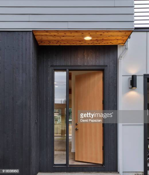 front door, brown front door of a modern house with the lights on - front door stock pictures, royalty-free photos & images