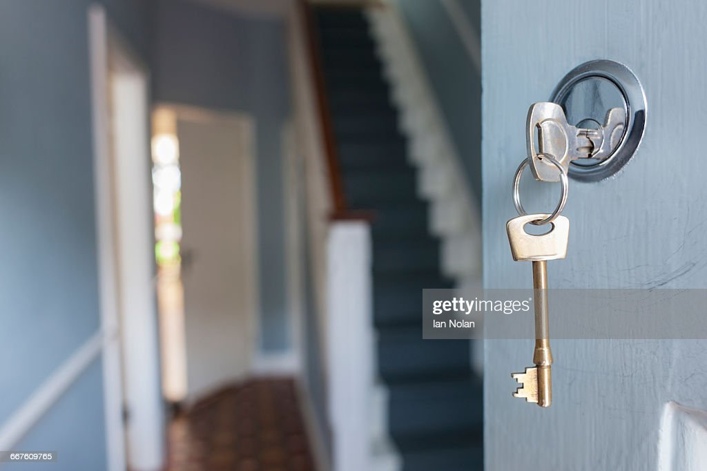Front door of house with key in lock : Stock Photo