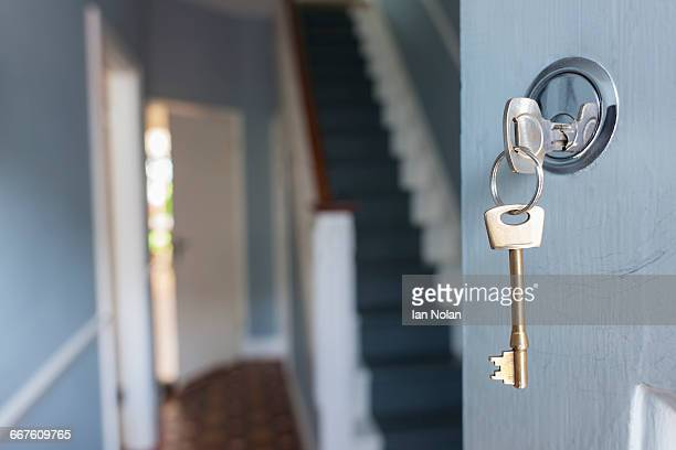 front door of house with key in lock - house key stock photos and pictures