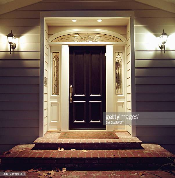 front door of house with lights at night - illuminate stock photos and pictures