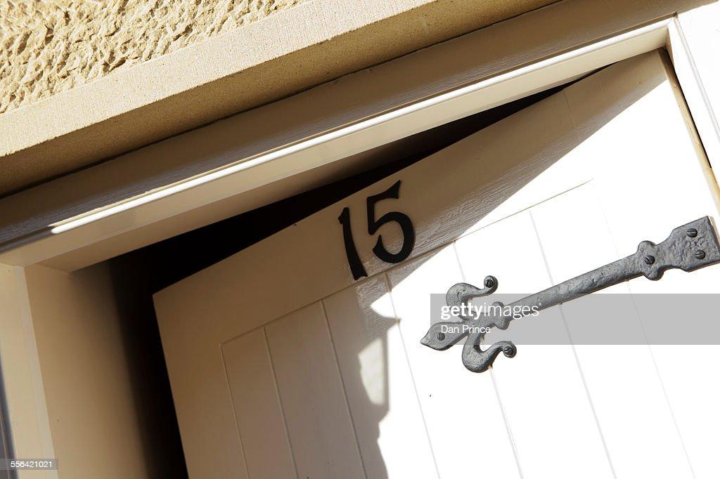 Front door, open ajar, number fifteen : Stock Photo