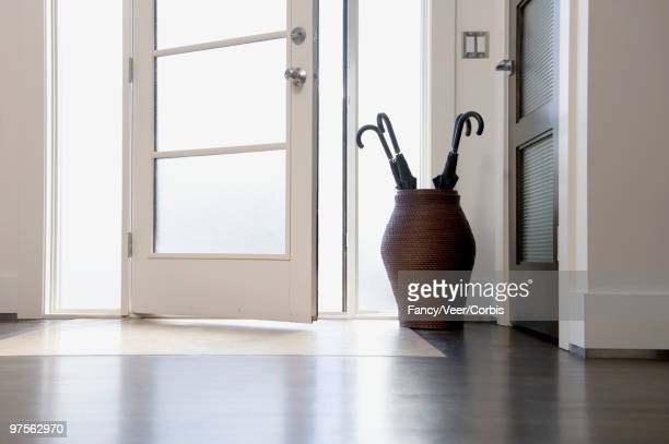 Front door with umbrellas in large vase