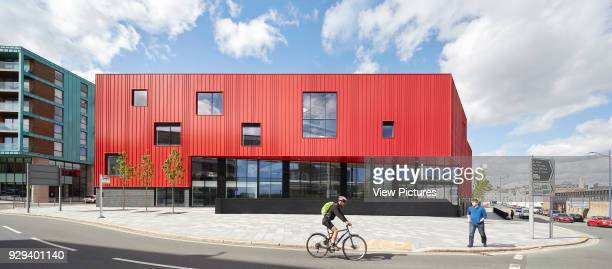 Front elevation of red facade with street passerby and bicyclist Plymouth Creative School of Art Plymouth United Kingdom Architect Feilden Clegg...
