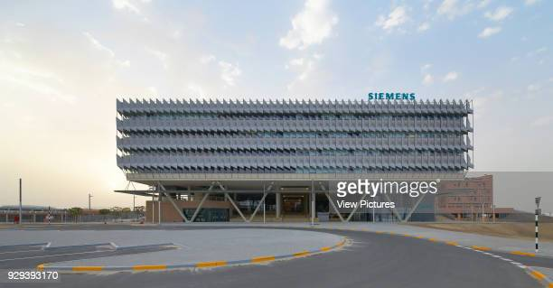 Front elevation with signage seen from approach. Siemens Masdar, Abu Dhabi, United Arab Emirates. Architect: Sheppard Robson, 2014.