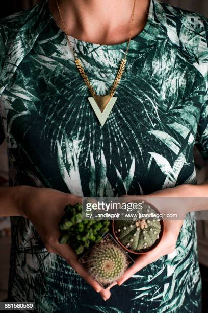 Front girl with green texture shirt holding three cactus pots